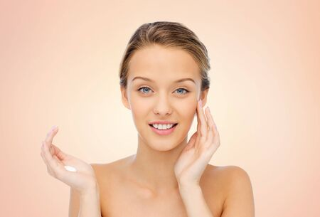 young woman face: happy smiling young woman applying cream to her face over beige background