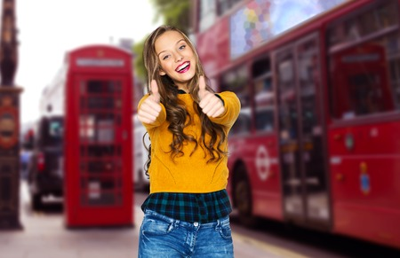 british girl: happy young woman or teen girl in casual clothes showing thumbs up over london city street background