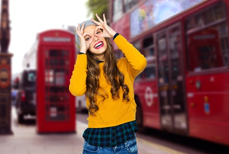 happy young woman or teen girl in casual clothes and hipster hat having fun over london city street background