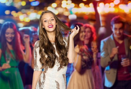 happy young woman or teen girl in fancy dress with sequins at night club party over crowd and lights background