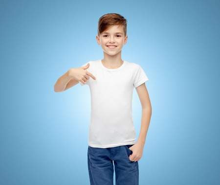 pre adolescent boys: happy boy in white t-shirt and jeans pointing finger to himself over blue background