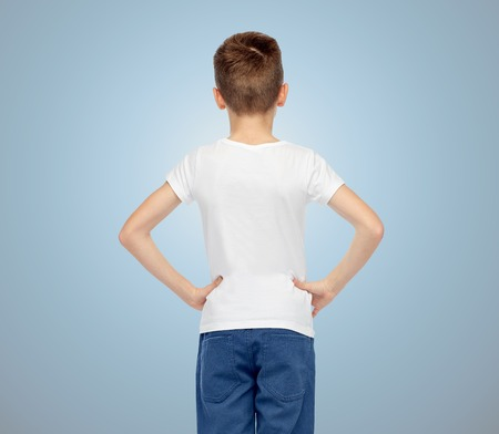 pre teen boy: boy in white t-shirt and jeans over blue background from back