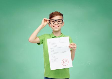 gelukkig lachend jongen in brillen bedrijf papier met testresultaat op groene school schoolbord achtergrond