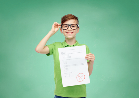 happy smiling boy in eyeglasses holding paper with test result over green school chalk board background