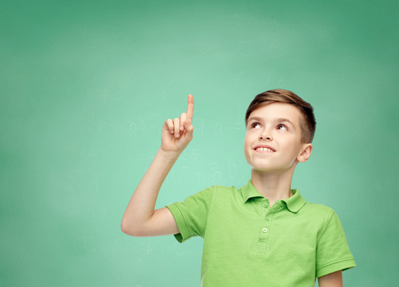 happy smiling boy in green polo t-shirt pointing finger up over green school chalk board background