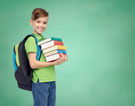 childhood, school, education and people concept - happy smiling student boy with school bag and books over green school chalk board background