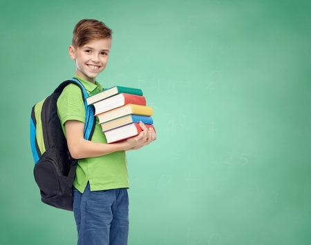 Kindheit, Schule, Bildung und Menschen Konzept - glücklich lächelnd Schüler Junge mit Schultasche und Bücher über Hintergrund grün Schule Kreidetafel