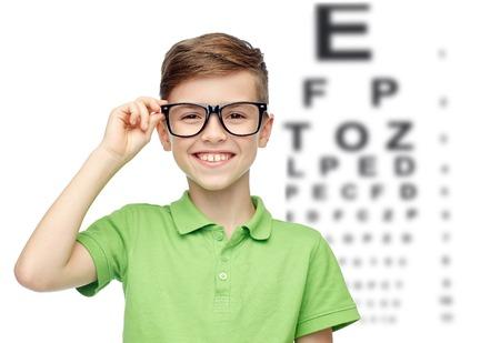 examen de la vista: feliz niño sonriente en verde camiseta del polo en los anteojos sobre carta de fondo de ojo Foto de archivo