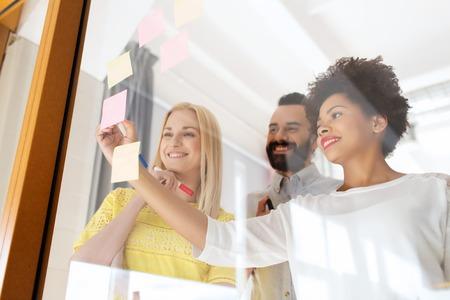 planificacion: escritura de feliz equipo creativo internacional sobre el parachoques en el tablero de cristal de la oficina