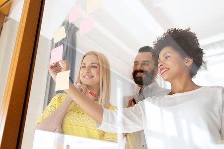 Equipe: heureux écrit internationale de l'équipe créative sur des autocollants à plaque de verre de bureau Banque d'images