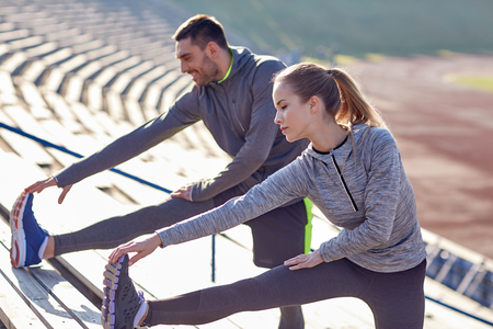 motion: par stretching ben på bestånd av stadion Stockfoto