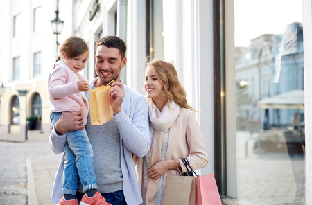 little town: happy family with little child and shopping bags in city