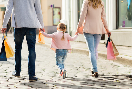 close up of happy family with little child and shopping bags in city