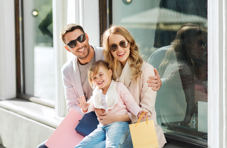 happy family with little child and shopping bags at shop window in city