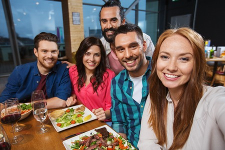 comiendo: amigos felices en la cena y teniendo autofoto por teléfono inteligente en el restaurante