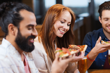 eating pizza: smiling friends eating pizza and drinking beer at restaurant or pub