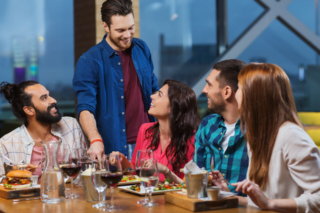 smiling friends having dinner and drinking red wine at restaurant Stock Photo