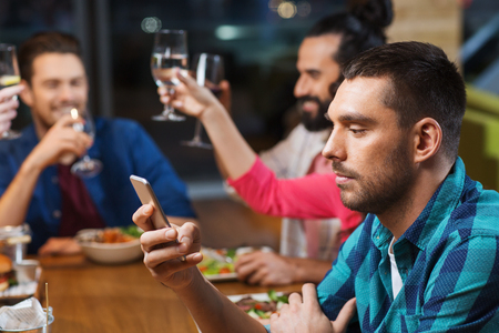 social gathering: man with smartphone and friends at restaurant