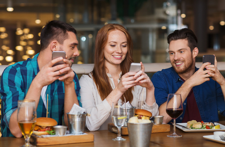 young: happy friends with smartphones dining at restaurant