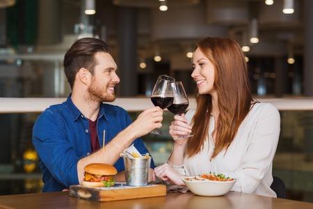 tomando vino: sonriente pareja cenando y bebiendo vino tinto en fecha en restaurante Foto de archivo