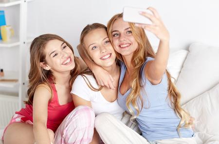 幸せな友人やスマート フォン selfie を取って自宅で 10 代の少女 写真素材 - 51808779