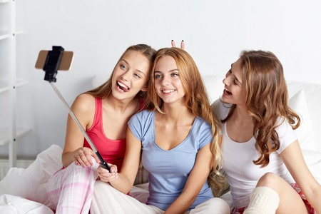 pj's: happy friends or teenage girls with smartphone and monopod taking selfie at home