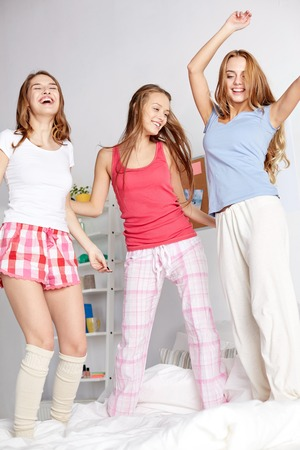pj's: happy friends or teenage girls having fun and jumping on bed at home