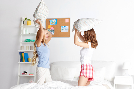pj's: happy friends or teenage girls having fun and pillow fight on bed at home