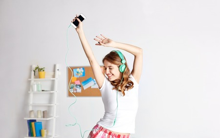 happy woman or teenage girl in headphones listening to music from smartphone and dancing on bed at home Stockfoto