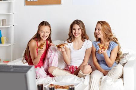 comiendo: amigos felices o adolescentes comiendo pizza y viendo la pel�cula o serie de televisi�n en el hogar Foto de archivo