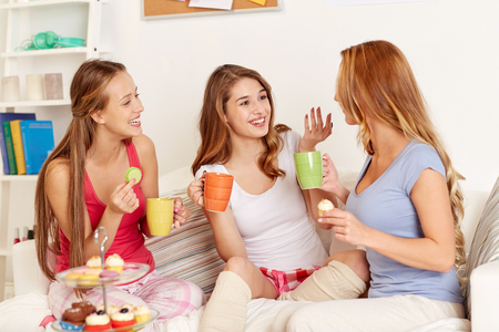 gossip: happy friends or teenage girls drinking tea and eating sweets at home