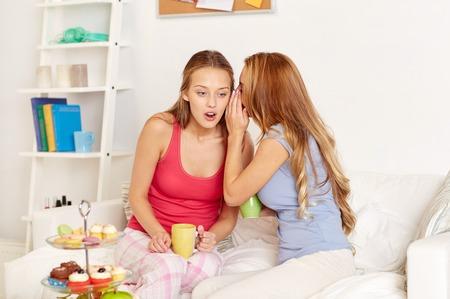 chismes: amigos felices o adolescentes beber t� con dulces y lo ajeno en el hogar Foto de archivo