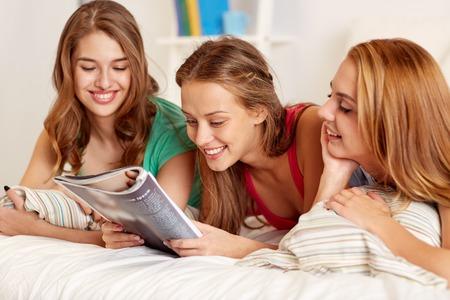 persona leyendo: amigos felices o adolescentes revista de lectura en la cama en su casa Foto de archivo