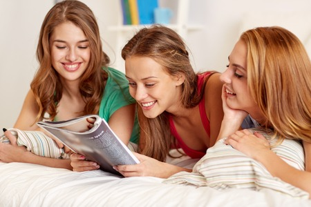 gl�ckliche Freunde oder junge M�dchen zu Hause und im Bett zu lesen