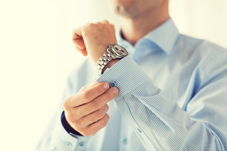 fastening: close up of man fastening buttons on shirt sleeve at home Stock Photo