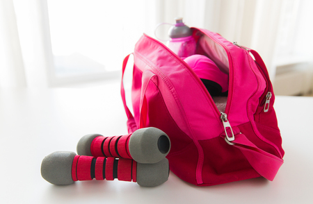 stuff: close up of female sports stuff in bag and dumbbells