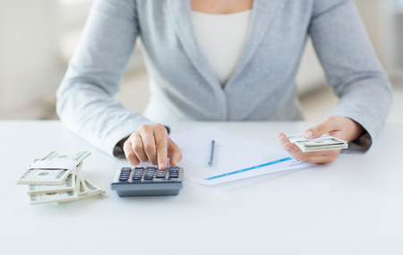 close up of woman hands counting us dollar money with calculator