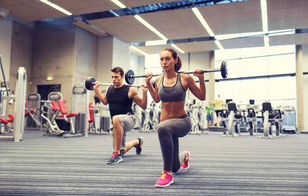 giovane uomo e donna con bilanciere flette i muscoli e rendendo spalla stampa affondo in palestra