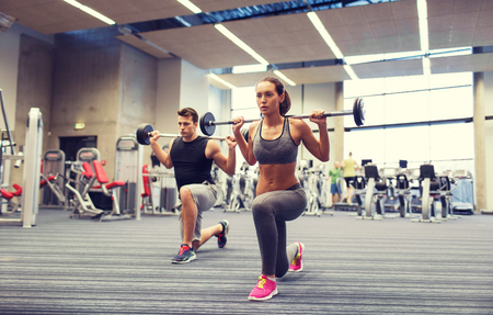gym workout: young man and woman with barbell flexing muscles and making shoulder press lunge in gym