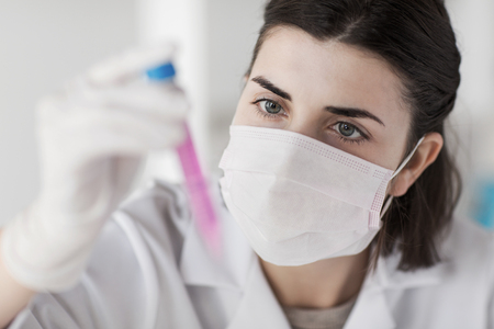 face mask: close up of young female scientist holding tube with sample making and test or research in clinical laboratory