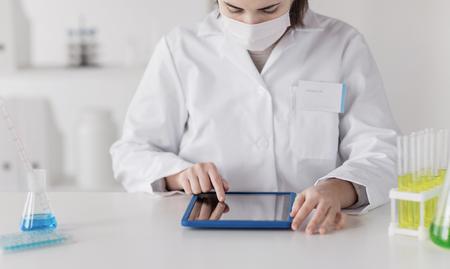 bata blanca: primer plano de mujer de ciencias joven con la prueba de la toma de la computadora Tablet PC o la investigación en laboratorio clínico