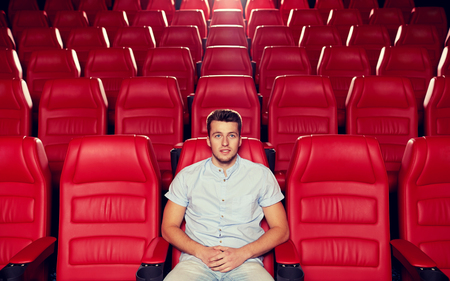happy young man watching movie alone in empty theater auditorium 스톡 콘텐츠