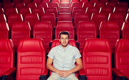 persona sentada: hombre joven feliz de ver películas solamente en auditorio vacío del teatro