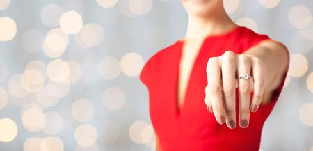 aniversario de boda: cerca del anillo de bodas muestra a la mujer en su mano sobre fondo de las luces