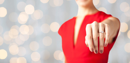 anniversario matrimonio: close up of woman showing wedding ring on her hand over lights background