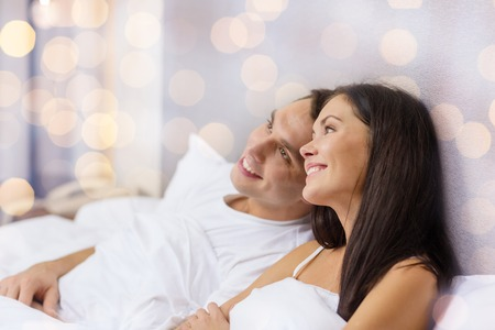 enamorados en la cama: feliz pareja soñando en la cama sobre fondo de las luces