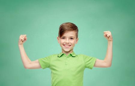 gelukkig lachend jongen in groene polo t-shirt die sterke vuisten op groene school schoolbord achtergrond