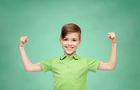 strong: happy smiling boy in green polo t-shirt showing strong fists over green school chalk board background Stock Photo