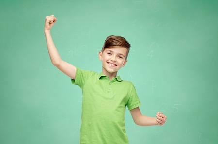 緑の学校のチョーク ボードの背景にグリーンのポロに幸せな笑みを浮かべて少年を強く見せ t シャツ拳します。