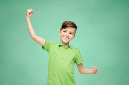 pre adolescent boys: happy smiling boy in green polo t-shirt showing strong fists over green school chalk board background Stock Photo